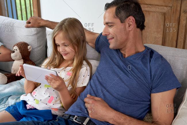 Dad watching daughter using tablet