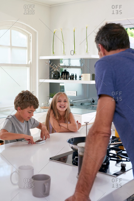 Dad making coffee in kitchen with kids