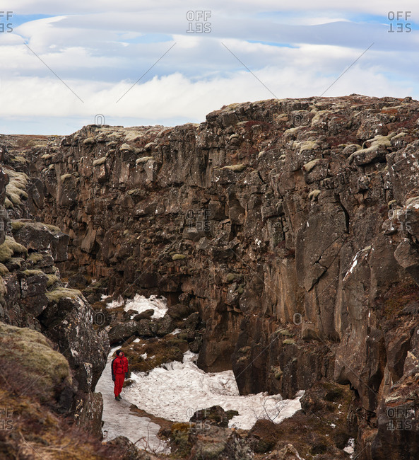 Man exploring impressive lava rock formations in tectonic plate crack crevice valley in thingvellir national park iceland