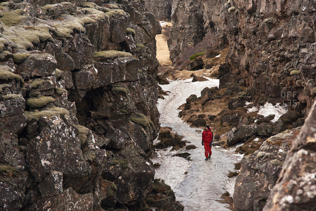 Man exploring lava rock formations in tectonic plate crack crevice valley in Thingvellir National Park