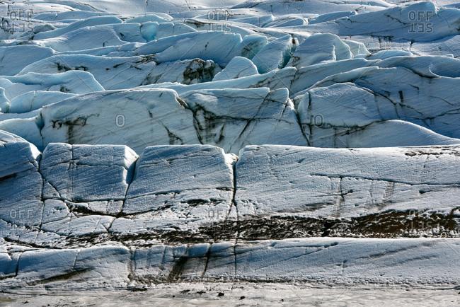 Snowy blue icy texture of a arctic glacier with black cracks