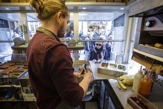 Copenhagen, Denmark - May 3, 2014: Worker at DOP, an organic hotdog stand