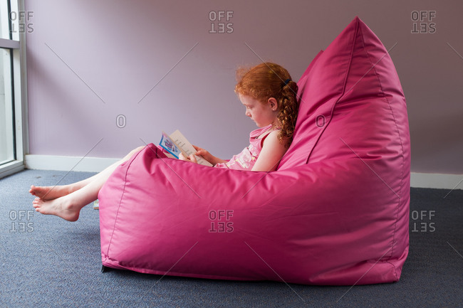 Girl sitting in a bean bag chair reading a book