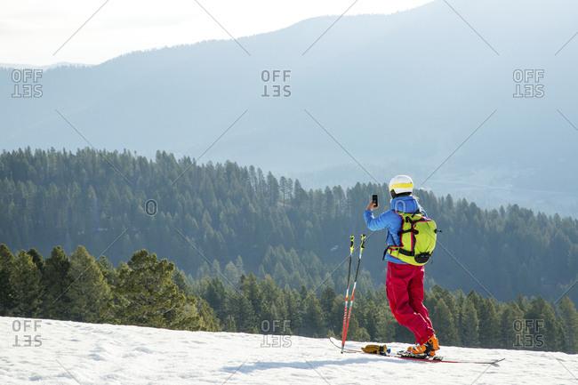 Woman taking a photo on the ski slopes