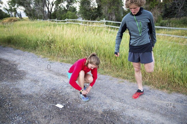 Young couple on a gravel path warming up for a run