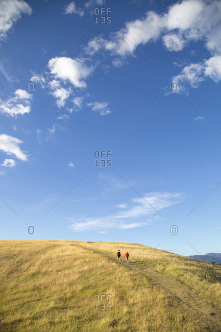 Couple running on a scenic rural hill
