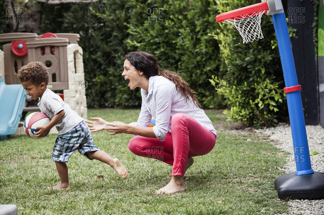 Woman playing basketball with her son in the backyard