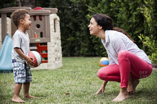 Boy and his mother playing basketball in the backyard