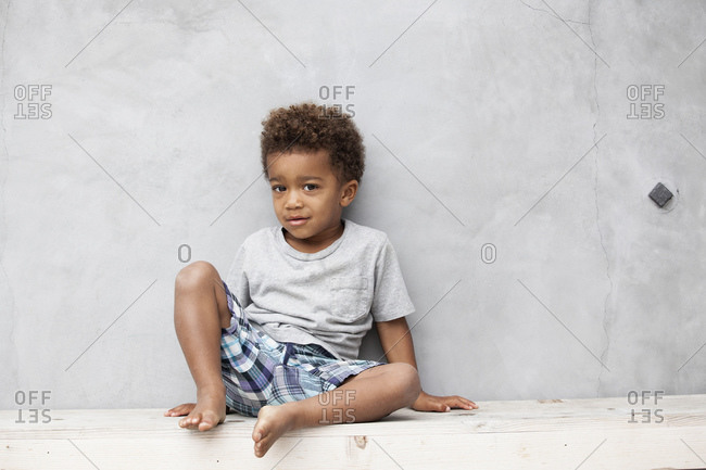Portrait of a little boy sitting against a cement wall