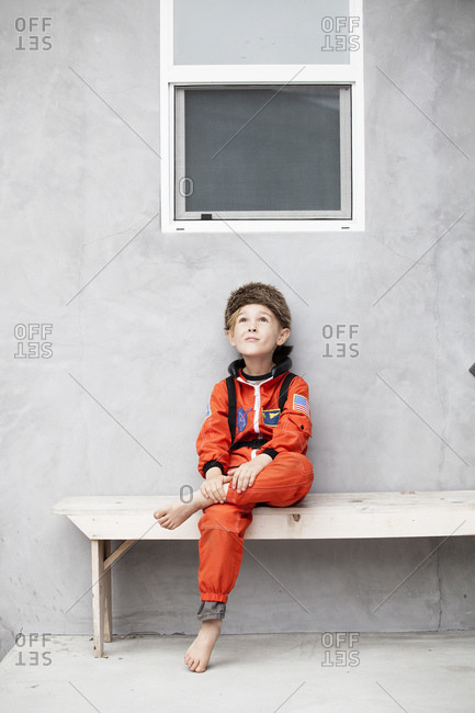 Boy in an astronaut costume sitting on a wooden bench