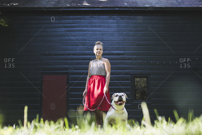 Woman with her dog standing in front of a rustic black barn