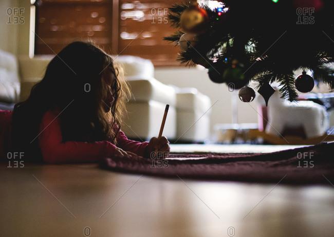 Girl writing letter under Christmas tree