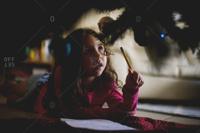 Girl writing a letter under Christmas tree