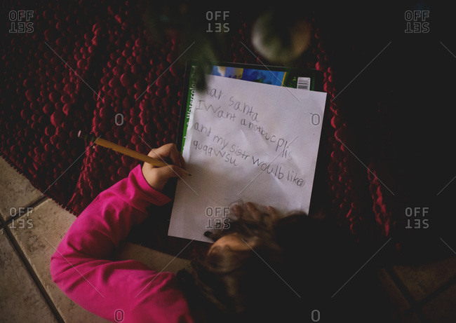 Girl writing letter under a Christmas tree