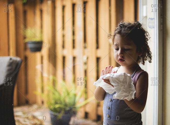 Girl holding paper towel by window