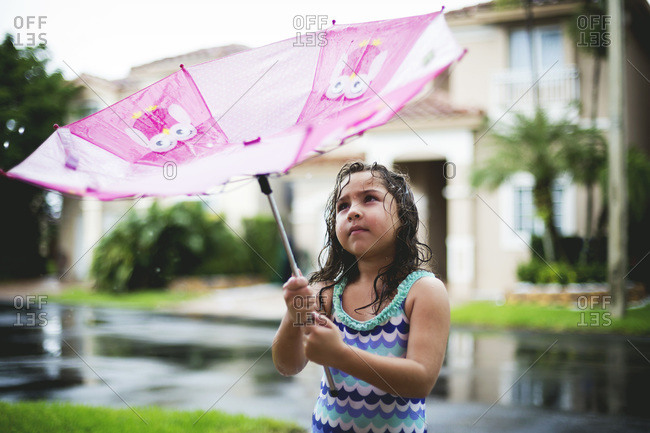 Young girl playing in a rain with an umbrella