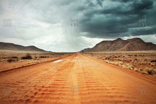 Desert road with distant storm, Namibia