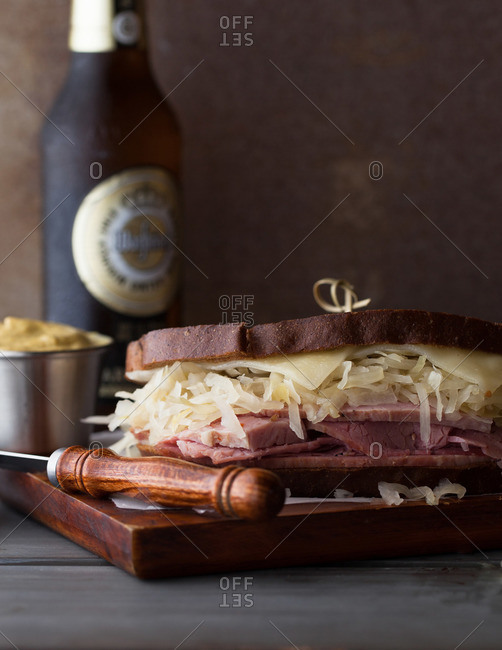 Pastrami sandwich with spicy mustard and beer on cutting board