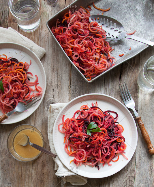 Spiralized cooked beet dish being served onto plates at table setting