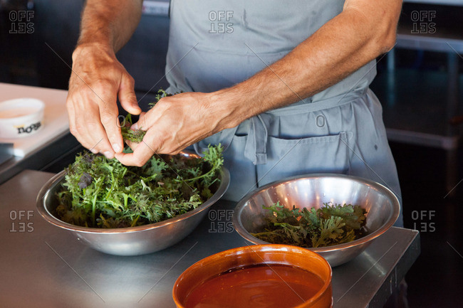 Male chef's hands putting greens into bowl