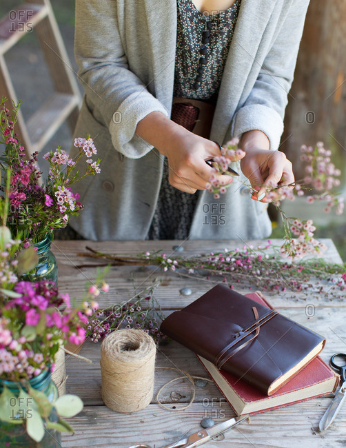 Woman trimming wild flowers on a rustic table