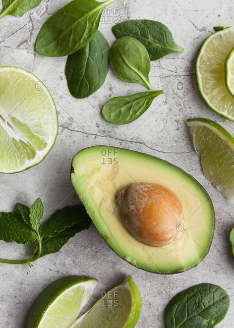 Avocado with limes, mint and spinach on marble background