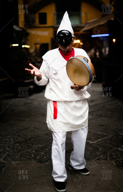 Man dressed in white costume with a tambourine