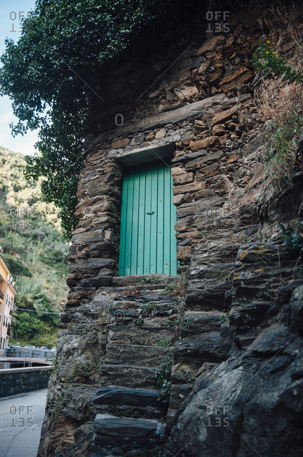 Green door on a stone building in Italy