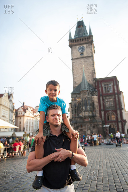 Father and son walking by Old Town Hall, Prague, Czech Republic