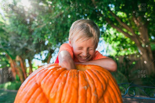 Boy reaching inside a large, hollowed-out pumpkin