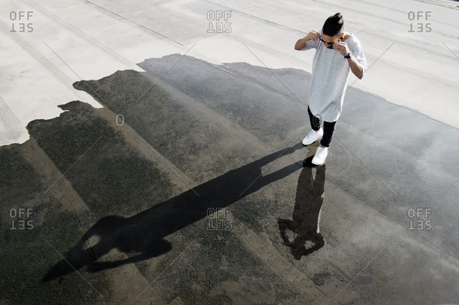 Young man standing in a puddle on a rooftop