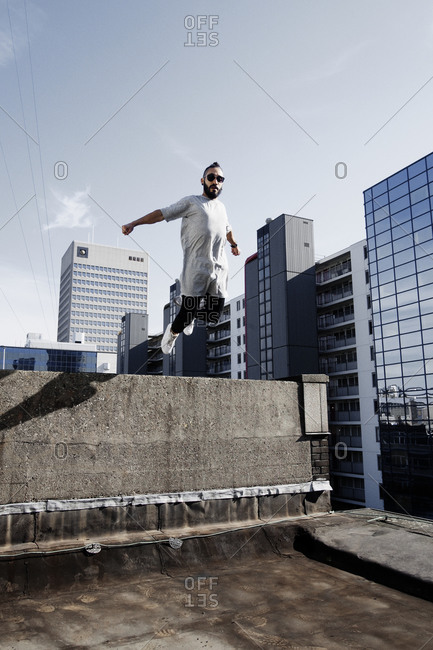 Young man doing parkour on a rooftop