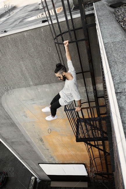 Young man doing parkour on a fire escape