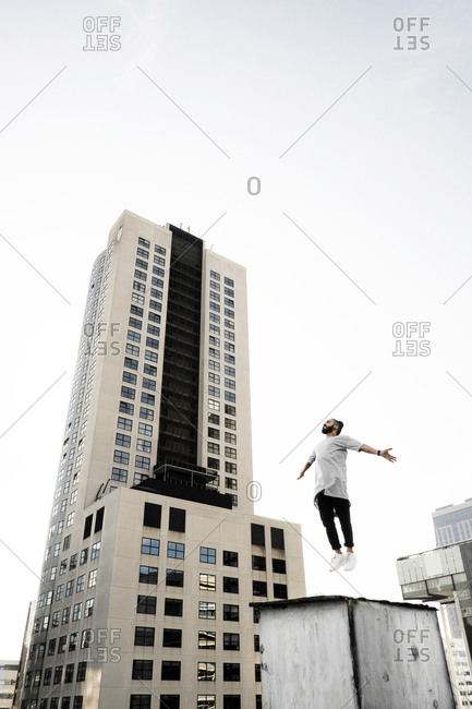 Young man jumping up on a rooftop