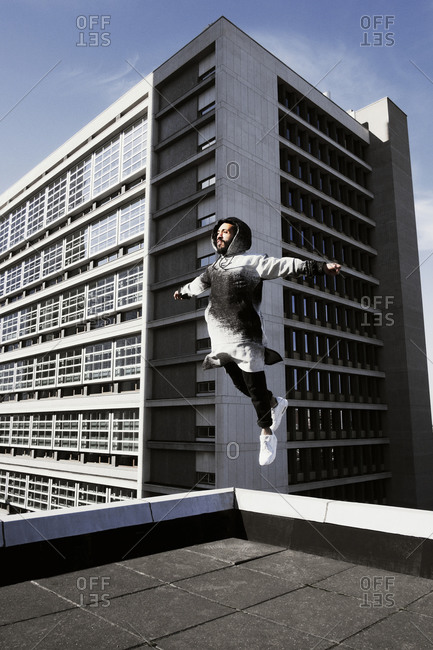 Young man leaping on a rooftop