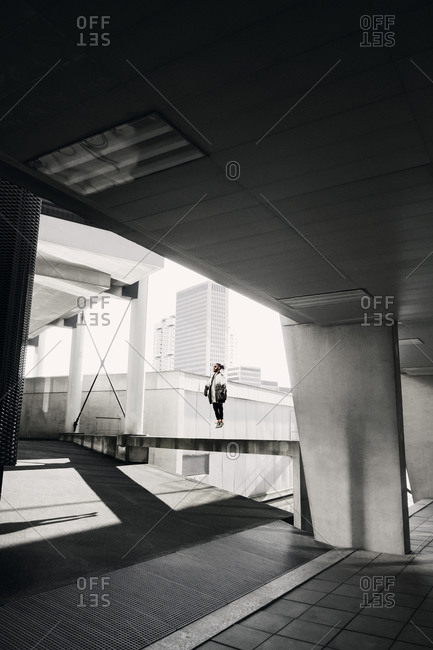 Young man jumping at modern urban building