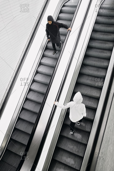 Two people going up and down an escalator
