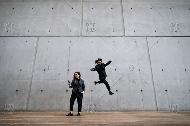 Man doing parkour behind a woman on a smartphone