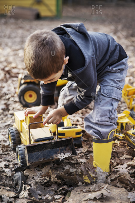 Boy playing with toy trucks in late fall