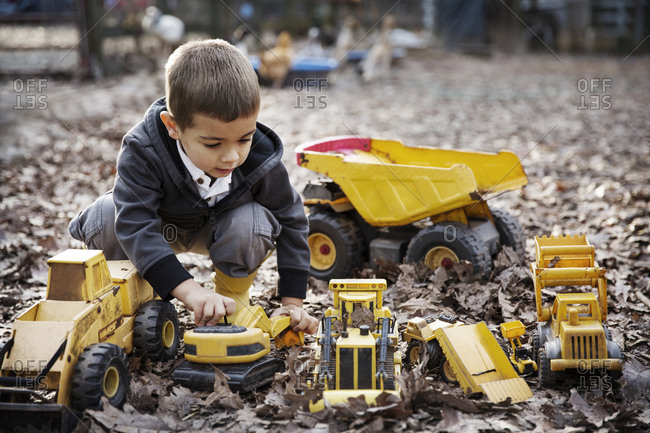 Boy playing with toy trucks in fallen leaves