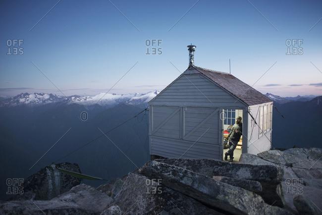 Man enjoying twilight at Hidden Lake Peak Fire Lookout cabin in Washington