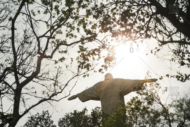 Christ the Redeemer statue seen through trees in Rio de Janeiro, Brazil