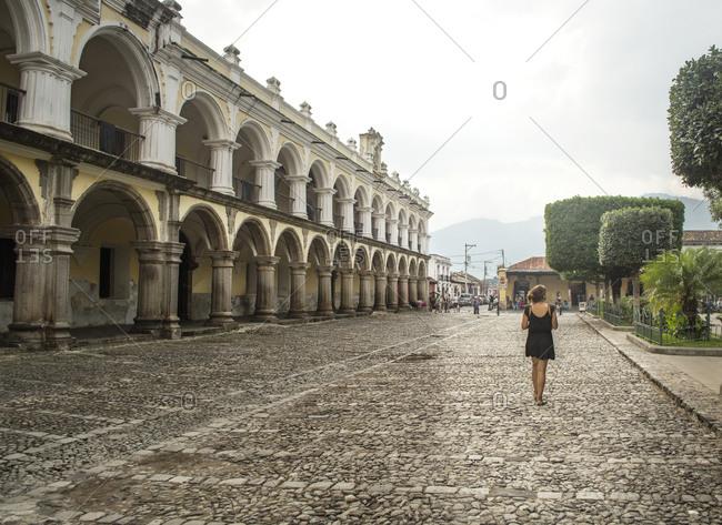 Woman walking next to the Palacio de los Capitanes Generals in Antigua, Guatemala