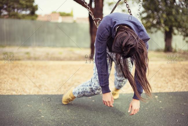 Girl hanging on a swing set