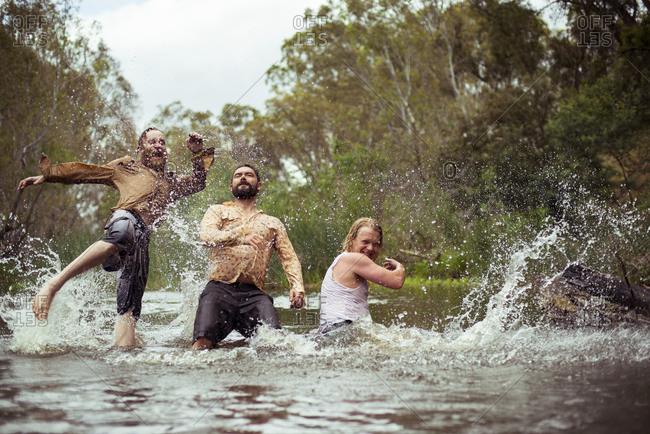 Male friends goofing around in water