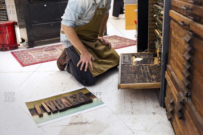 Printmaker selecting type in a letterpress workshop