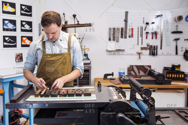 Man laying out type in a letterpress workshop