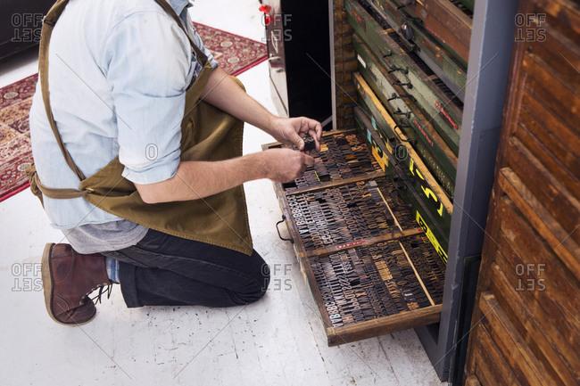 Man choosing type in a letterpress workshop