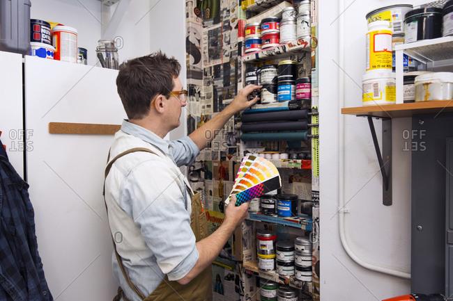 Printmaker selecting ink colors in a workshop