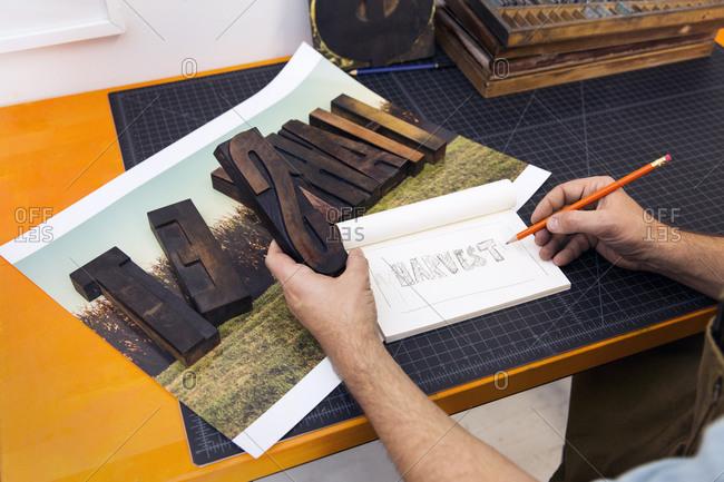 Printmaker sketching ideas in a letterpress studio